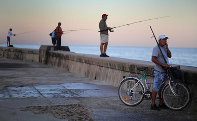 A man smokes a cigarette as people fish on the Malecon in Havana