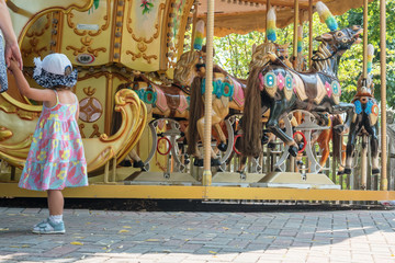 little girl holding her mother by the hand near the merry-go-round with horses in the park