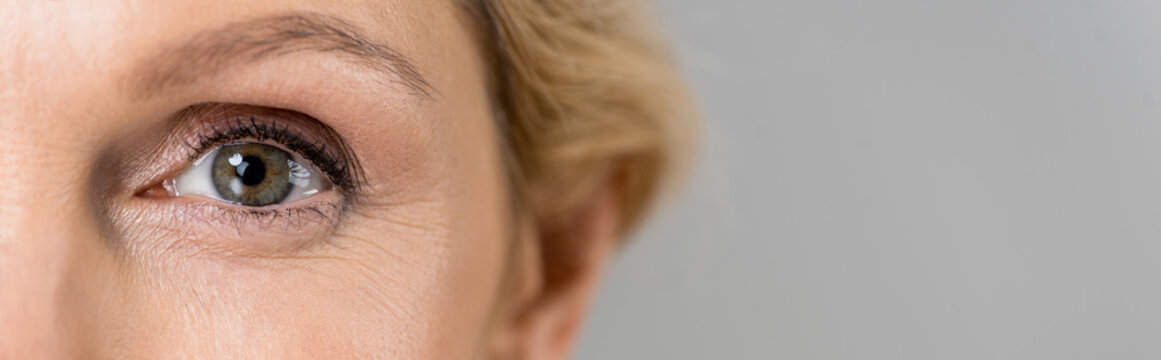panoramic shot of mature woman looking at camera isolated on grey