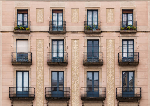 Windows and balconies in row on facade of historic building