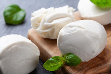 Photo sur Aluminium Buffalo Mozzarella cheese with basil on wooden board. Natural italian dairy product.
