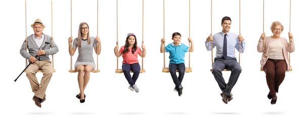 Grandparents, parents and children sitting on swings and smiling at the camera