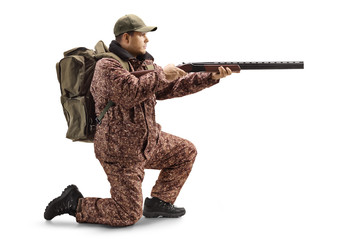 Man hunter in a uniform kneeling and aiming with a shotgun Wall mural