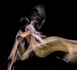one caucasian young woman modern  dancer dancing isolated on black background with  light painting...