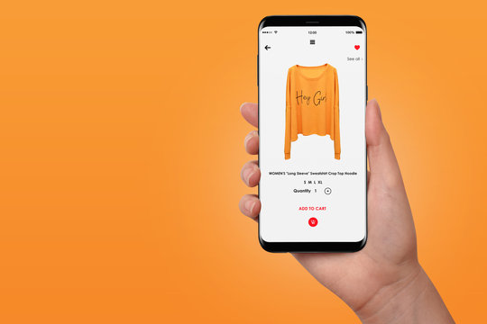 Female hand buying yellow hoodie online on her phone, isolated on orange background