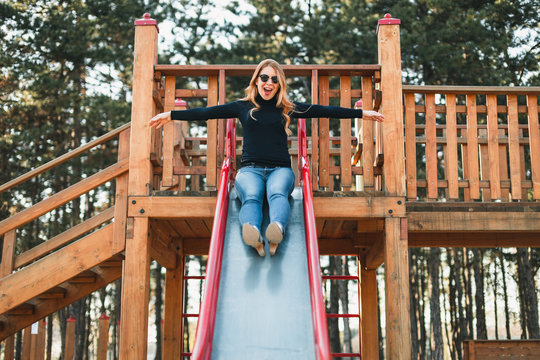 Young happy woman enjoying on the slide in the public playground