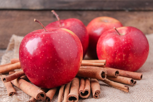 cinnamon sticks and apples on wooden background