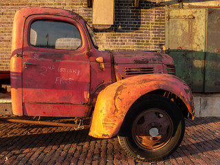 old red truck cab  parked in alley