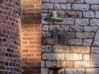old brick wall with green antique light fixture