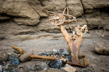 rusted, discarded bicycle parts at bottom of cliff
