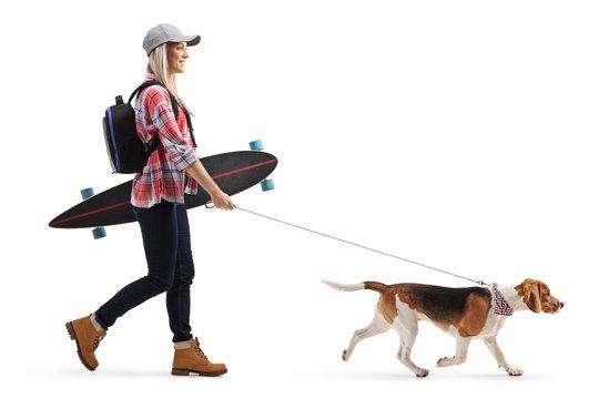 Female skater with a longboard walking a beagle dog