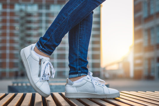 Woman wearing jeans and white sneakers is standing in city after sunset