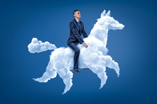 Young businessman riding white cloud horse on blue background
