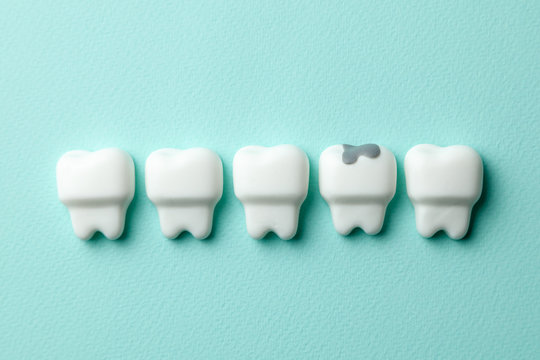 Healthy white teeth and tooth with caries on green mint background.