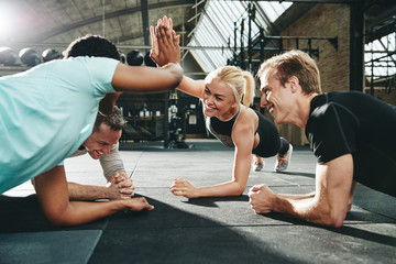 Laughing women high fiving together while planking at the gym