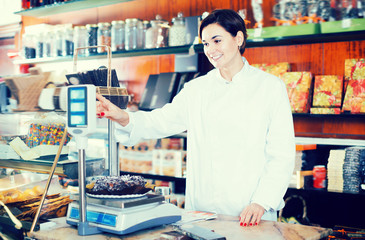 Young seller weighing festive chocolate cake