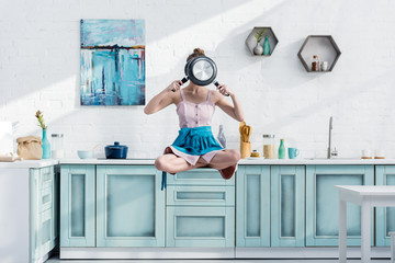 young woman flying in air in lotus pose with pans in front of face