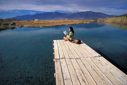 Woman reading book while sitting on pier over river against mountains