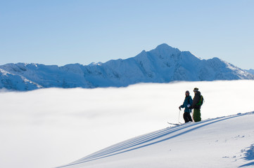 Mark Abma and Sean Pettit taking in the view while traversing on skiis above the clouds with mountain range in background in Mustang Powder Cats mountain area, BC, Canada.
