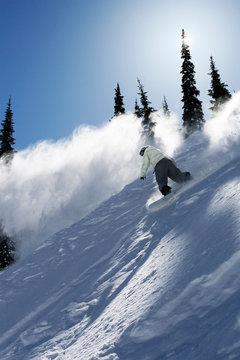 A male snowboarder ripping powder at Schweitzer Mountain Resort, Idaho (back lit).