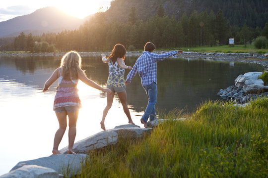 Three young adults walk along the shoreline at sunset in Sandpoint, Idaho.