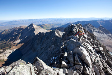 A young man crossing an exposed ridge line at the summit of Capitol mountain. Capitol is one the hardest 14ers in Colorado to climb.