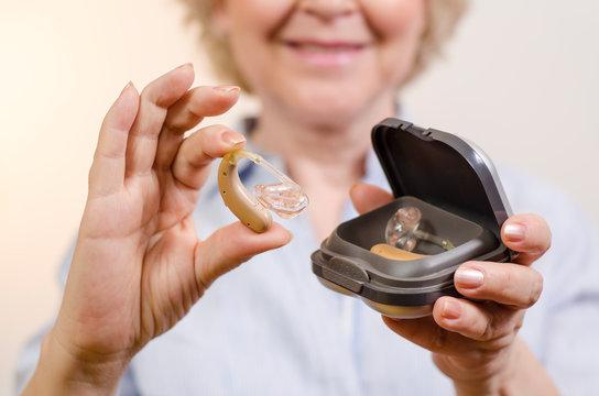 Closeup shot, unrecognizable senior unboxing hearing aid