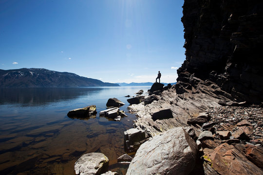 A male figure stands on a rock at the edge of a beautiful lake on a sunny day in Sandpoint, Idaho.