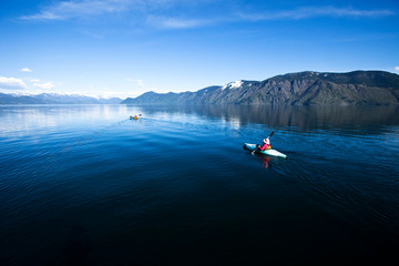 An happy adventurous retired couple kayaking on a huge calm lake in Sandpoint, Idaho.