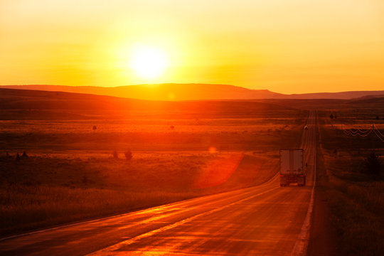 A shipping truck on a long straight highway at sunrise in Bozeman, Montana.