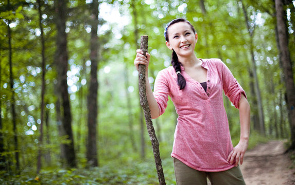 A smiling young woman stops on a trail while hiking in Monte Sano State Park, Huntsville, Alabama.