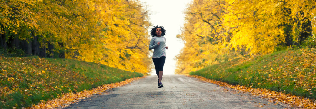 Woman jogging on country road in Autumn