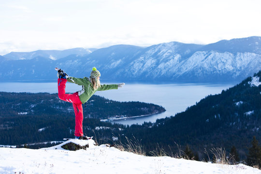 Woman practicing yoga on a snowy mountain