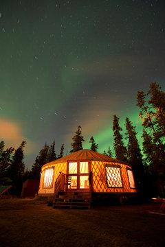 Northern Lights over illuminated yurt, Yukon, Canada