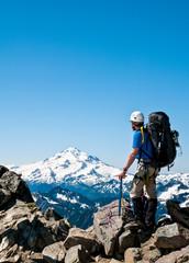 Climber on top of the Dana Glacier with Glacier peak in background, North Cascades, Washington