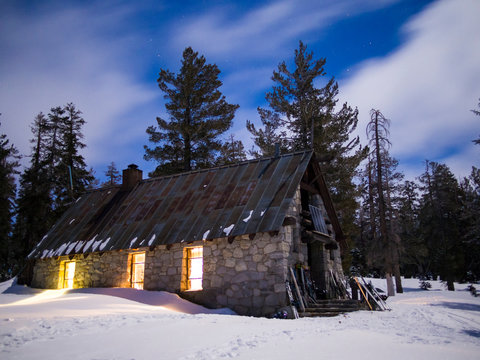 Night image of the Ostrander Hut with glowing windows and star filled sky.   The Ostrander Hut is the the premiere back country ski hut in the Sierra Nevada range, located 10 miles into the Yosemite Backcountry accessable only by skis or snowshoes, Yosemite National Park, California