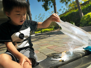 Boy plays with a magnifying glass and ignites a piece of paper.