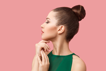 Profile side view portrait of calm serious beautiful young woman with bun hairstyle and makeup in green dress standing with closed eyes and touching her chin. studio shot, isolated on pink background.
