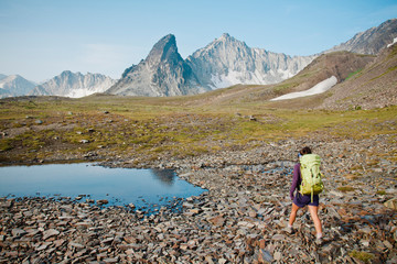 A female backpacker walks across scree and past a small tarn on her way towards the mountain range in the distance.
