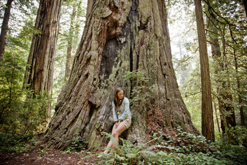A young woman leans against the trunk of a large old Redwood tree.