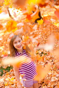 a little girl throws a handful of leaves into the air