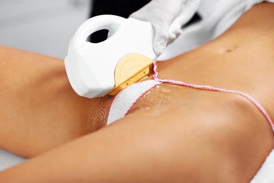 Beautician Giving Epilation Laser Treatment To Woman On Bikini