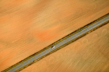 An aerial view of a car traveling on a paved road.