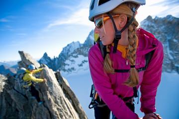 Two women climbing rocky peak