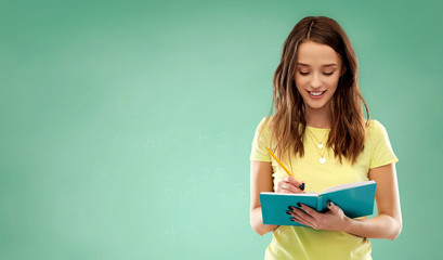education, school, inspiration and people concept - smiling teenage student girl in yellow t-shirt writing to diary or notebook by pencil over green chalk board background