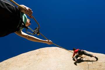 Sarah Felchlin (left) belaying Mitch Underhill while rock climbing at Owens River Gorge near Bishop, California.