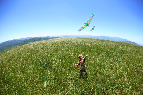 Young boy flies a toy glider along the Appalachian Trail on the summit of Max Patch Bald west of Asheville, NC