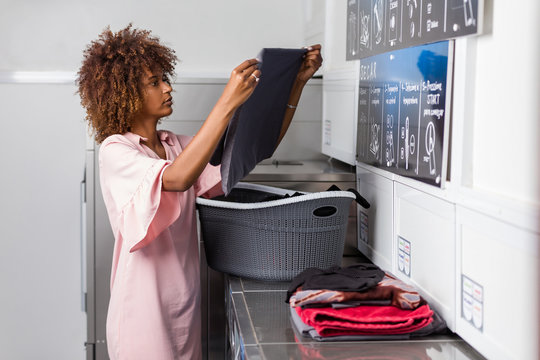 Young black African American woman washing her clothes in a automatic laundry