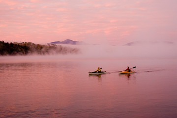 Fit, middle-age couple sea-kayak on Lake Placid at sunrise in autumn, New York, USA