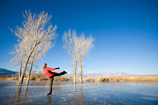 Woman ice skating on frozen pond